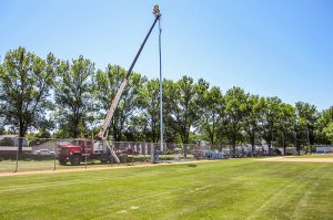 Cole's Electrical crew installing light at baseball field